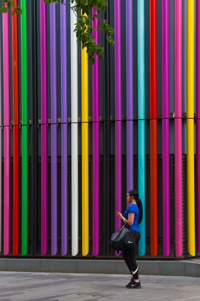 woman standing near the multicolored building wall at daytime